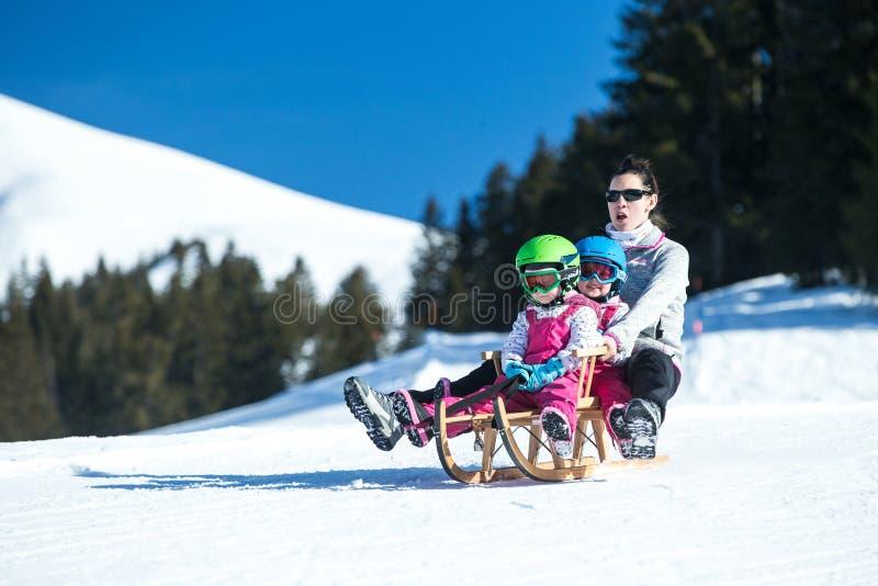 获得的母亲和的孩子在爬犁的乐趣有阿尔卑斯山panoramatic看法  活跃妈妈和小孩哄骗与安全帽 免版税图库摄影