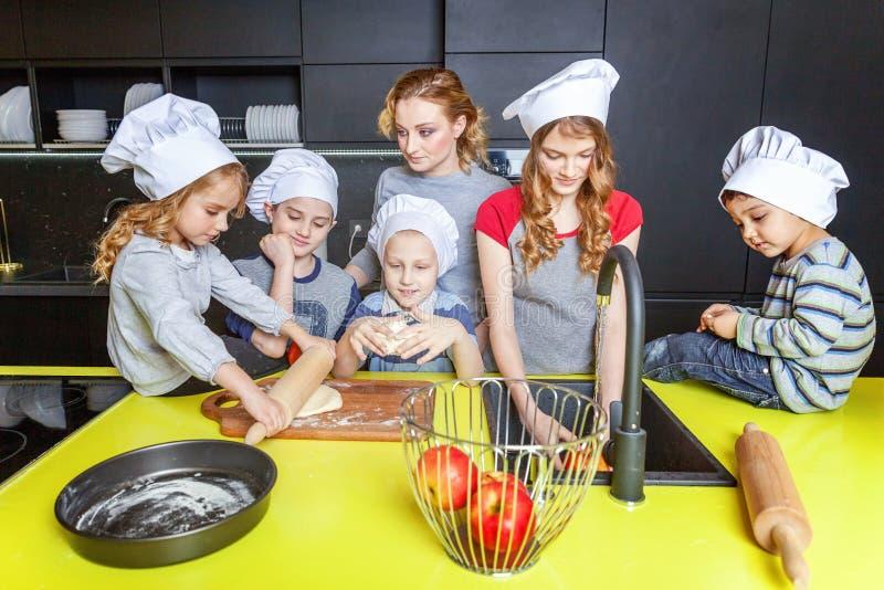 获得的母亲和的孩子烹调在厨房里和乐趣 免版税库存照片
