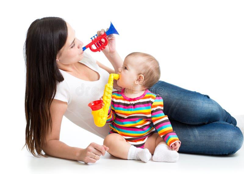 获得的母亲和的婴孩与音乐玩具的乐趣 背景查出的白色 免版税库存照片