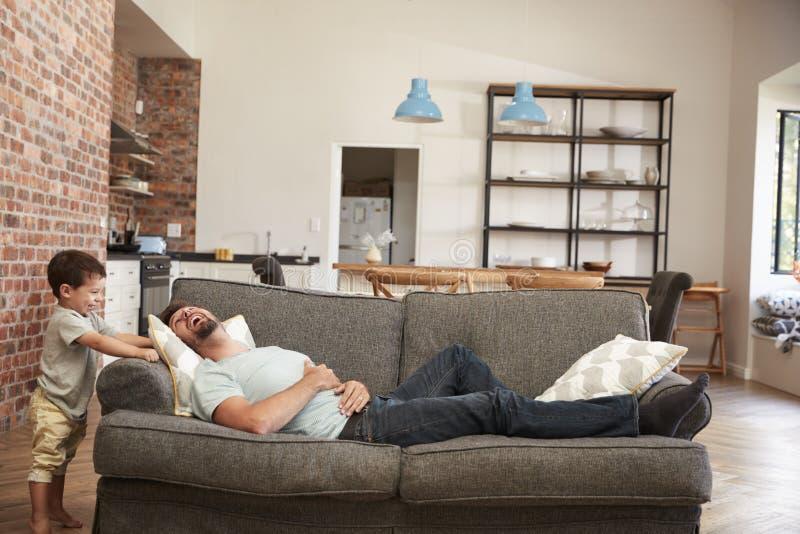 获得的父亲和的儿子一起使用在沙发的乐趣 免版税图库摄影
