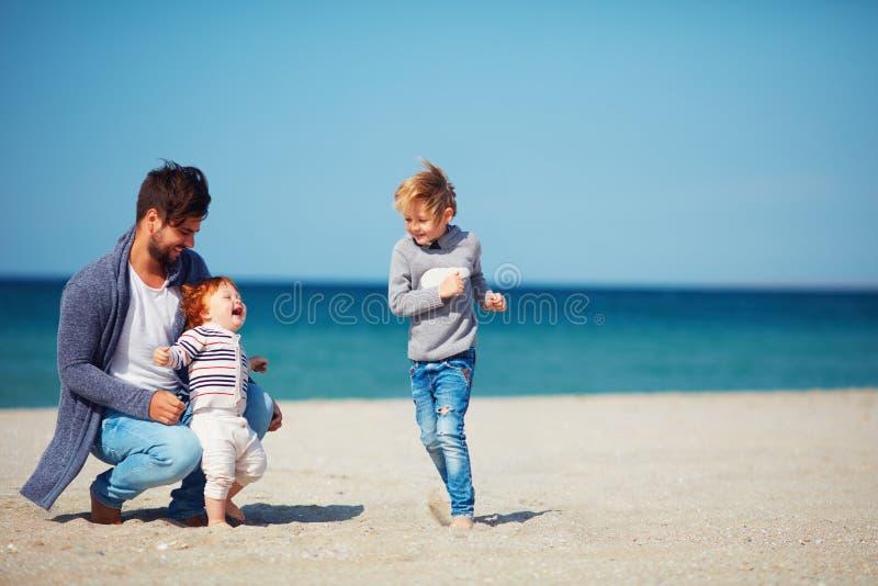 获得的父亲和的儿子乐趣,跑在沙滩 免版税库存图片
