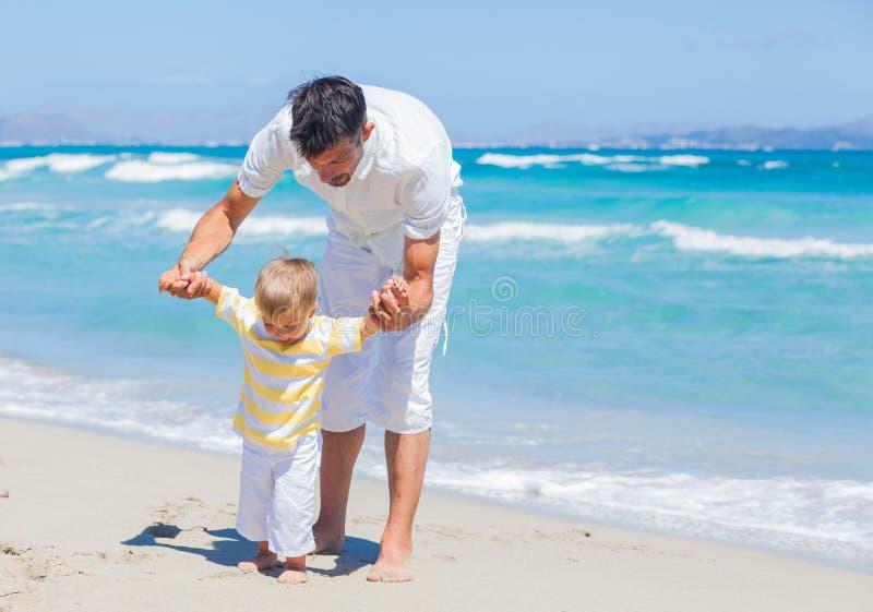 获得的父亲和的儿子在海滩的乐趣 免版税库存照片