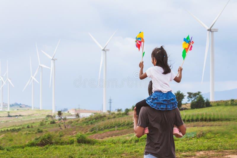获得的父亲和的女儿一起使用的乐趣 使用与风轮机和乘坐在父亲的肩膀的亚裔儿童女孩 图库摄影