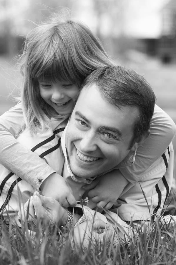 获得的父亲和的女儿在春天草甸的乐趣 免版税库存照片