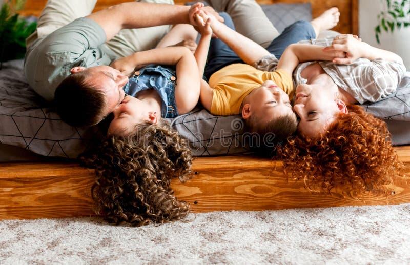 获得的父母与他们的两个小孩的乐趣在床上 库存图片