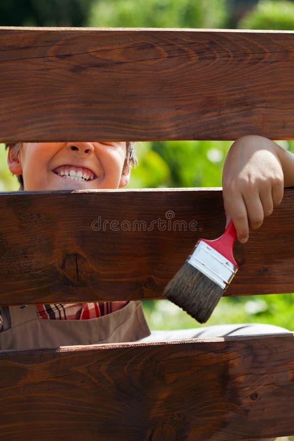 获得的男孩做鬼脸通过篱芭的乐趣-,当绘它时 免版税库存照片