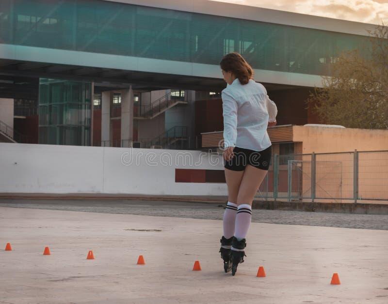 获得美丽的年轻女人与溜冰鞋的乐趣 免版税库存图片
