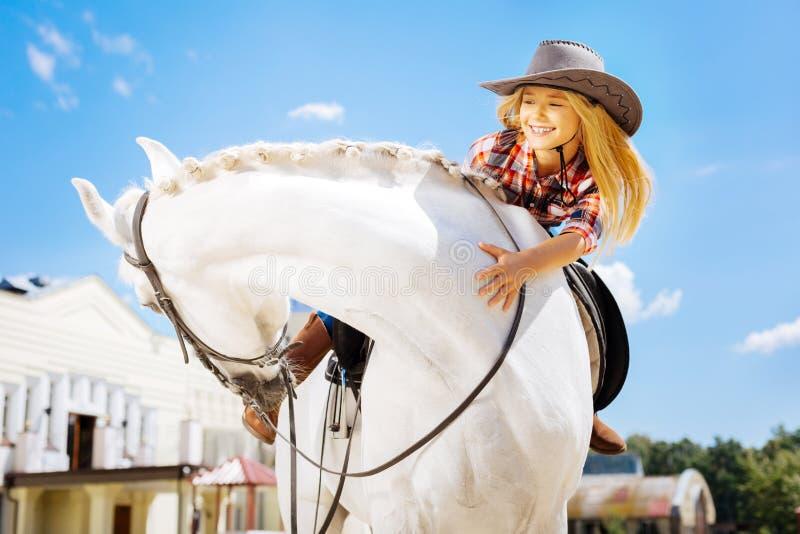 获得美丽的牛仔的女孩乐趣,当骑她可爱的马时 免版税库存照片