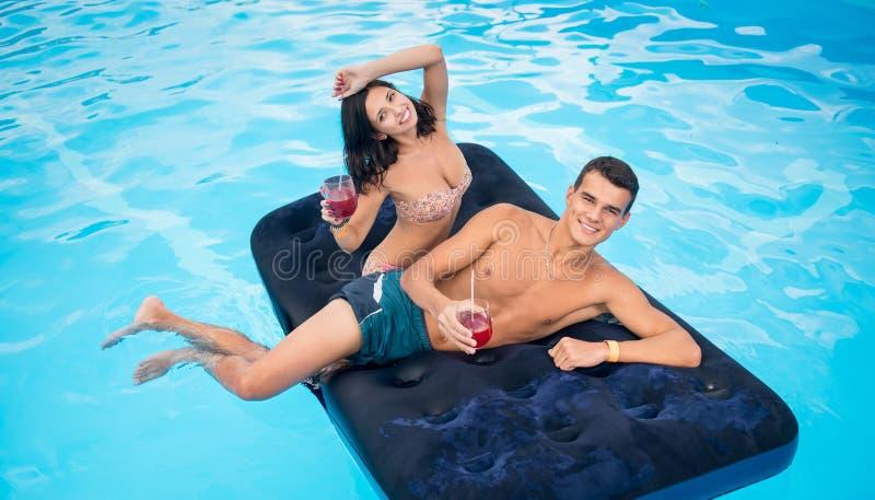 获得美好的对漂浮在游泳池,饮用的鸡尾酒的床垫和乐趣他们的暑假 库存图片