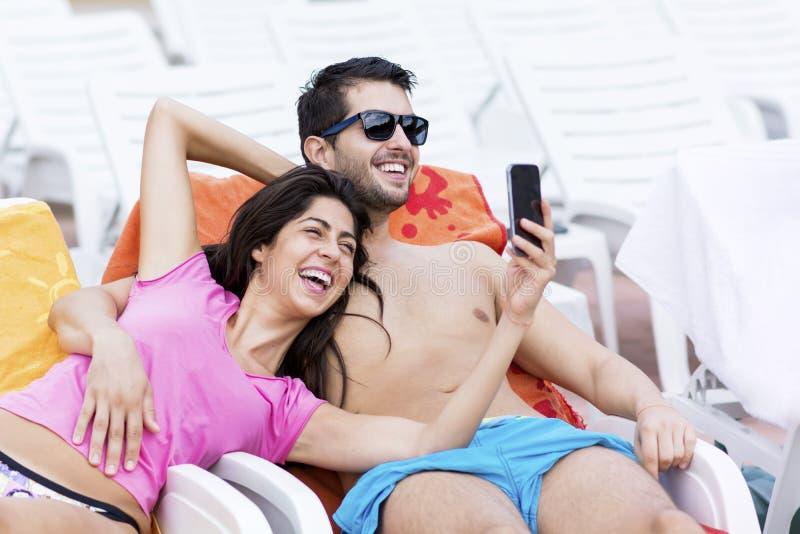 获得美好的年轻微笑的夫妇做selfie的乐趣 免版税图库摄影