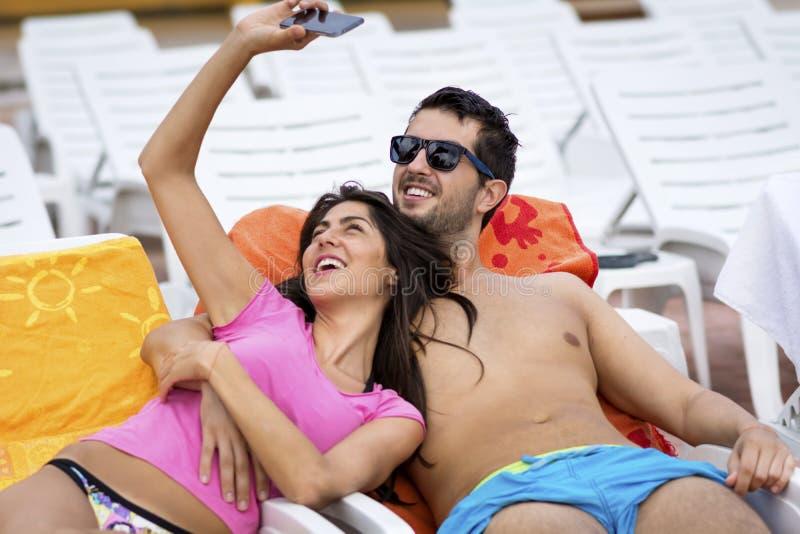 获得美好的年轻微笑的夫妇做selfie的乐趣 免版税库存图片