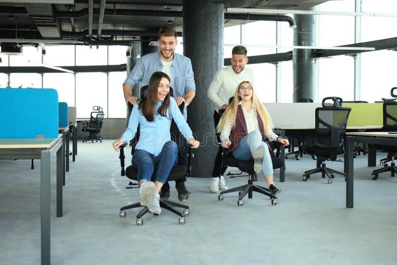 获得聪明的便衣的年轻快乐的商人乐趣,当赛跑在办公室椅子和微笑时 免版税库存照片