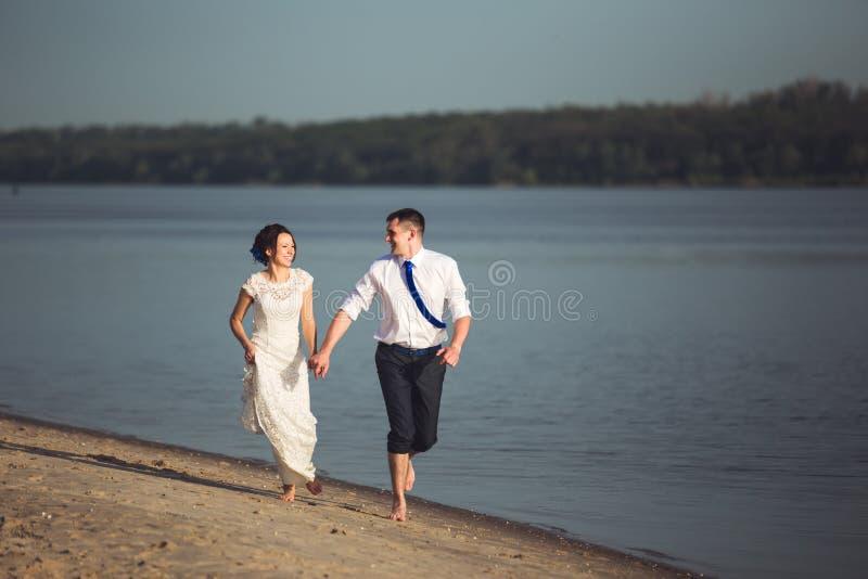 获得肉欲的年轻愉快的夫妇庆祝他们的在海滩的爱和乐趣 被定调子的图象 库存照片