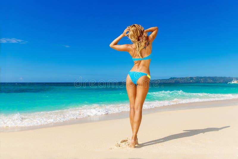 获得蓝色的比基尼泳装的年轻美丽的女孩在一热带bea的乐趣 库存照片