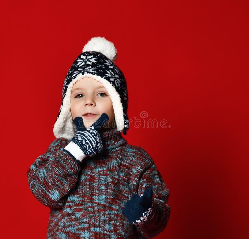 获得被编织的帽子的儿童男孩和的毛线衣和的手套在五颜六色的红色背景的乐趣 图库摄影