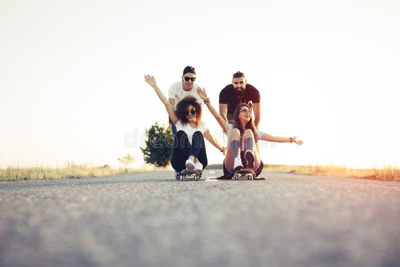 获得踩滑板的朋友乐趣 免版税图库摄影