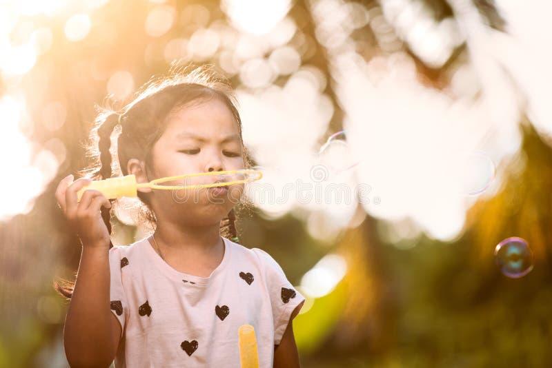 获得逗人喜爱的亚裔儿童的女孩吹的乐趣在室外的肥皂泡 免版税库存图片