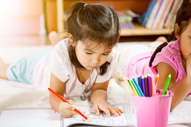 获得逗人喜爱的亚裔的小女孩乐趣绘与蜡笔 免版税图库摄影