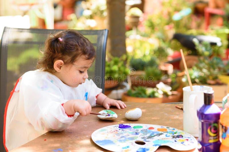 获得逗人喜爱的女孩乐趣,上色与刷子,文字和绘在夏天或秋天庭院 免版税库存照片