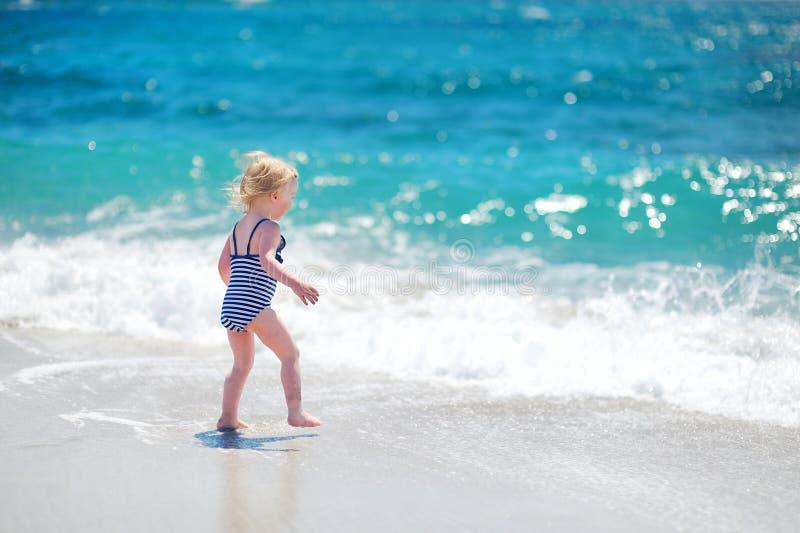 获得逗人喜爱的女孩在一个美丽的晴朗的海滩的乐趣 免版税图库摄影