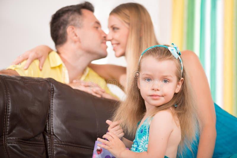 获得逗人喜爱的小女孩与父母的乐趣 库存图片