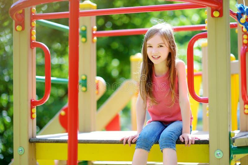获得逗人喜爱的小女孩在操场的乐趣户外 图库摄影