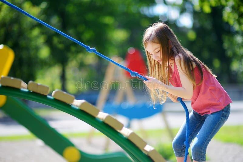 获得逗人喜爱的小女孩在操场的乐趣 库存图片