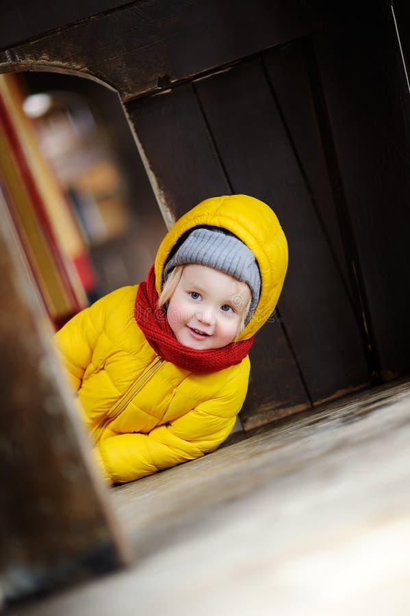 获得逗人喜爱的小男孩在室外操场的乐趣 演奏里面木儿童小屋或小屋的小孩 免版税库存照片