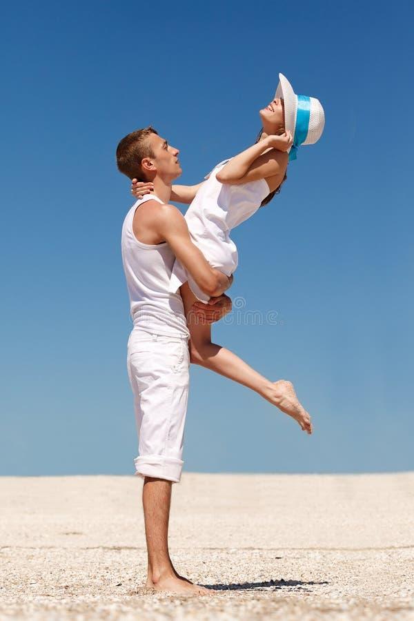 获得年轻的夫妇在海滩的乐趣 免版税库存图片