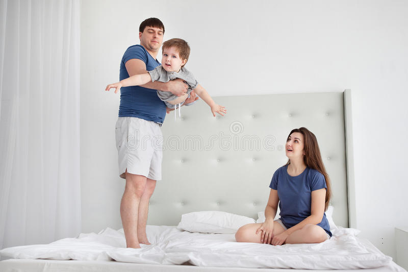 获得年轻的家庭弹起在床上的乐趣 免版税库存图片