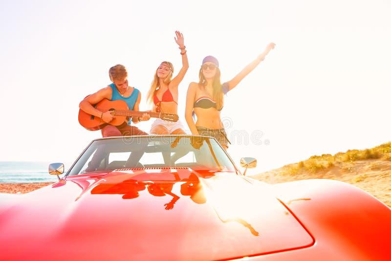获得年轻的小组在弹吉他的海滩的乐趣 免版税库存照片