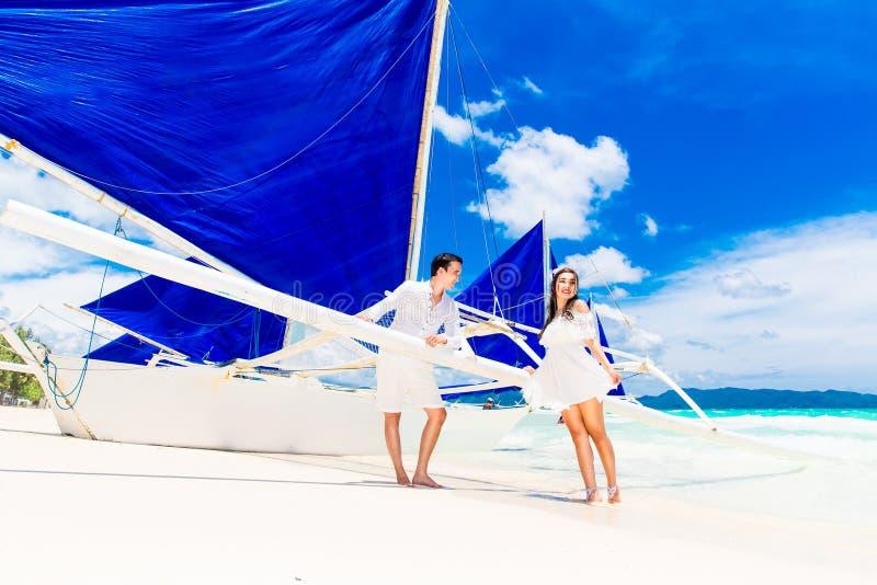获得年轻美好的夫妇在一个热带海滩的乐趣 Tropache 免版税库存图片