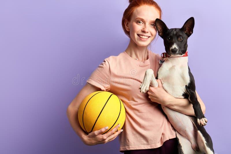 获得Cheeful正面的女孩与宠物的乐趣 免版税库存图片