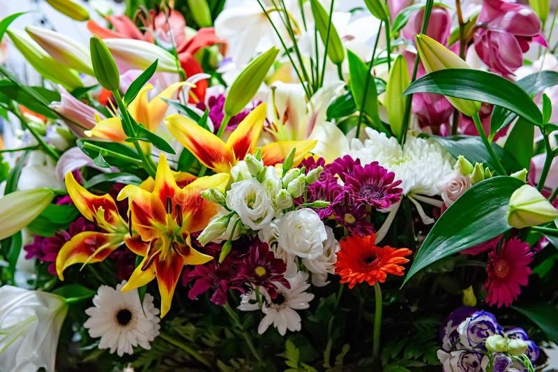 菊花、兰花和大丁草美丽的大花束与一个大黄色百合在花店 免版税库存照片