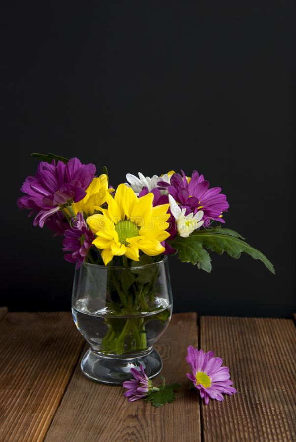 菊花的美好的秋天秋天花束安排在黑背景和木桌的玻璃开花 库存照片