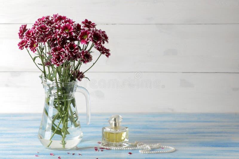菊花秋天花在水罐和香水的在一张蓝色木桌上 免版税库存图片