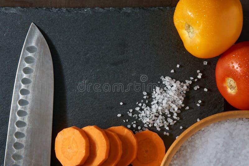菜、厨师刀子和海盐在板岩 免版税库存图片