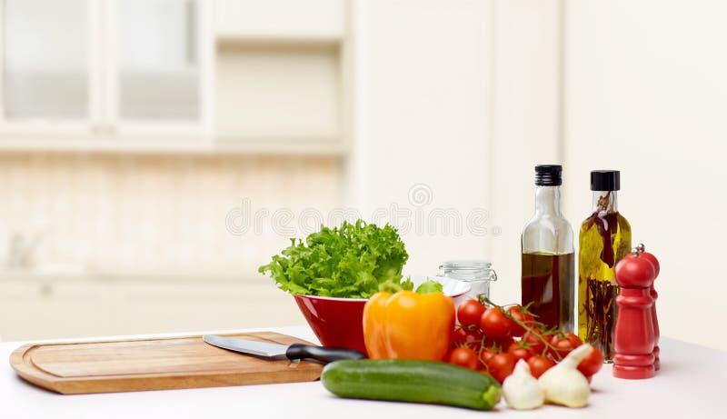 菜、香料和厨具在桌上 免版税库存图片
