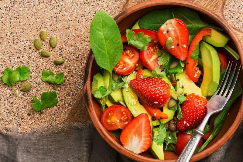 菜健康素食沙拉,鲕梨,菠菜,草莓,蕃茄,绿色,甜椒,种子 顶视图,拷贝空间 库存图片
