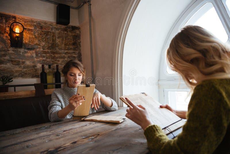 读菜单的妇女在餐馆 免版税库存图片