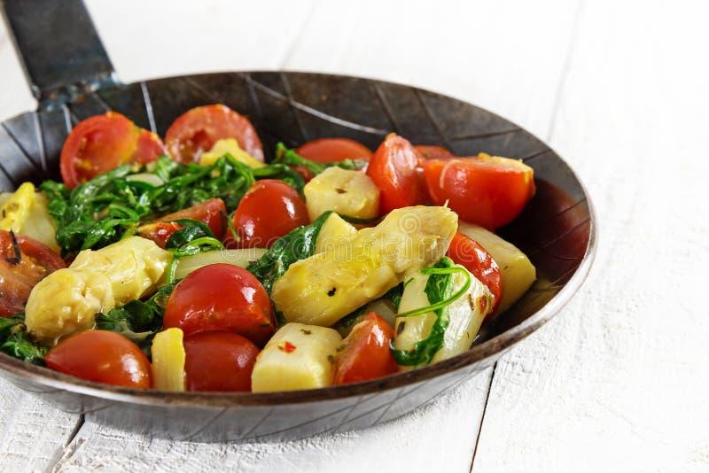 菜平底锅用油煎的芦笋、蕃茄和spinarch在w 库存照片