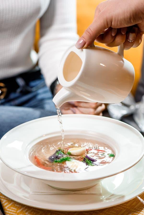 菜汤服务在餐馆 肉汤从一个白色茶壶倒入菜一块白色板材  库存图片