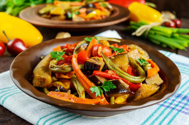 菜炖煮的食物沙拉:甜椒,茄子,芦笋豆,大蒜,红萝卜,韭葱 明亮的辣芳香盘 库存图片