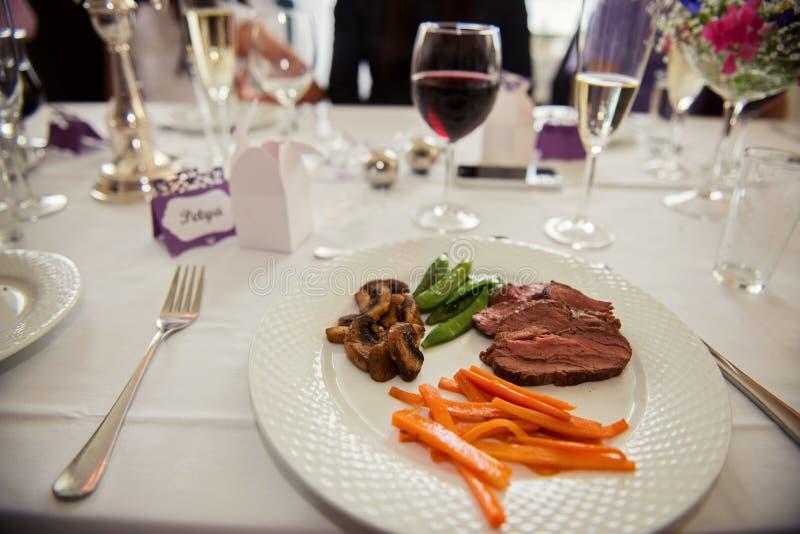 主菜菜单用牛肉、红萝卜、豆和蘑菇在一块白色板材新近地服务 免版税库存图片