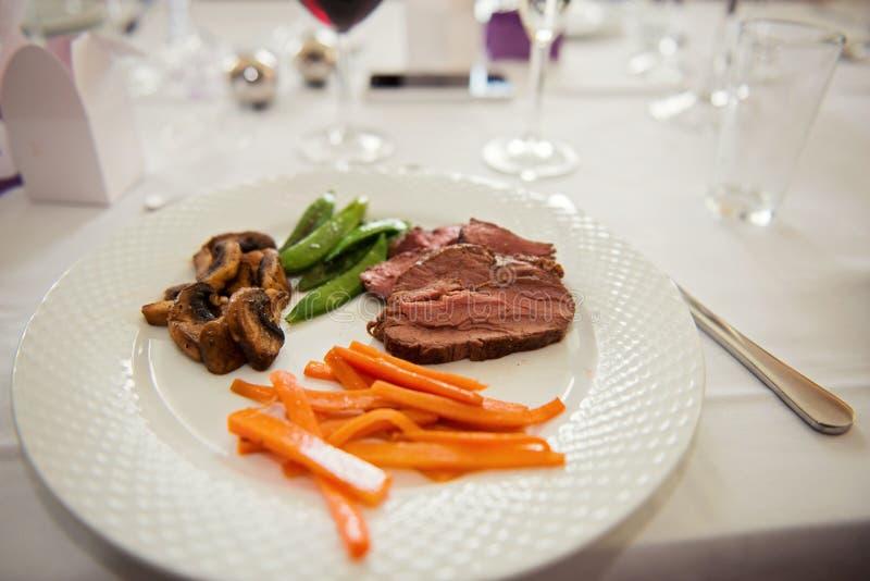 主菜菜单用牛肉、红萝卜、豆和蘑菇在一块白色板材新近地服务 免版税库存照片