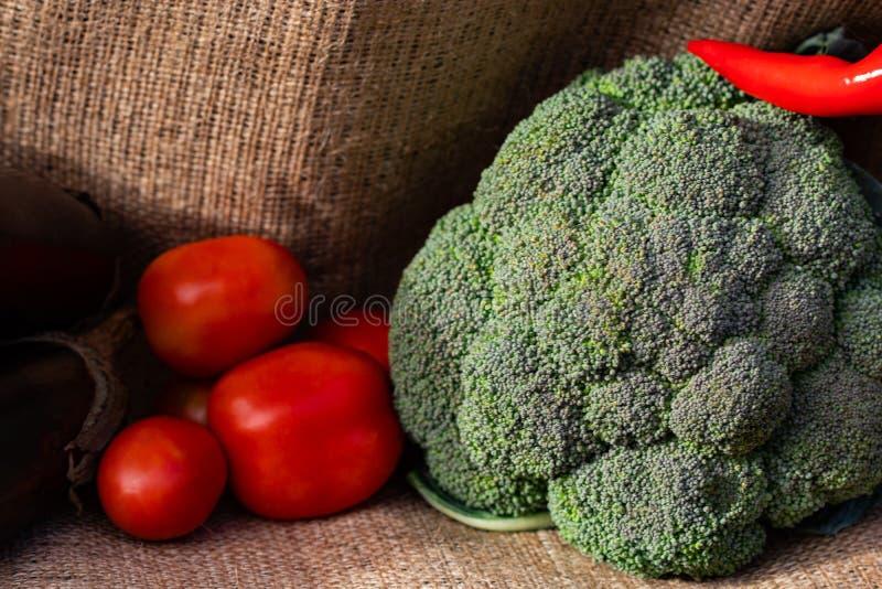 菜蕃茄和硬花甘蓝在粗麻布背景 免版税库存照片