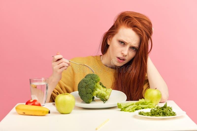 菜饮食 拿着在叉子的哀伤的愚钝的妇女硬花甘蓝,当做鬼脸时 免版税库存照片