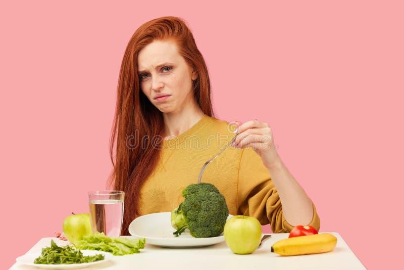 菜饮食 拿着在叉子的哀伤的愚钝的妇女硬花甘蓝,当做鬼脸时 库存照片
