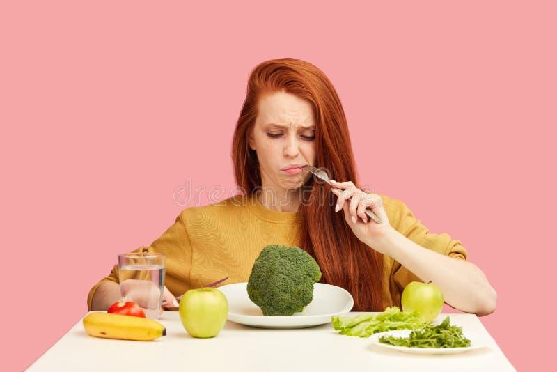 菜饮食 拿着在叉子的哀伤的愚钝的妇女硬花甘蓝,当做鬼脸时 库存图片