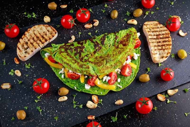菜绿色煎蛋卷用蕃茄,希腊乳酪,橄榄,坚果,辣椒粉,在石背景的多士 健康的概念 免版税库存照片